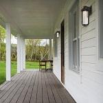 Long wooden porch of a modern farmhouse. Outdoors photography.
